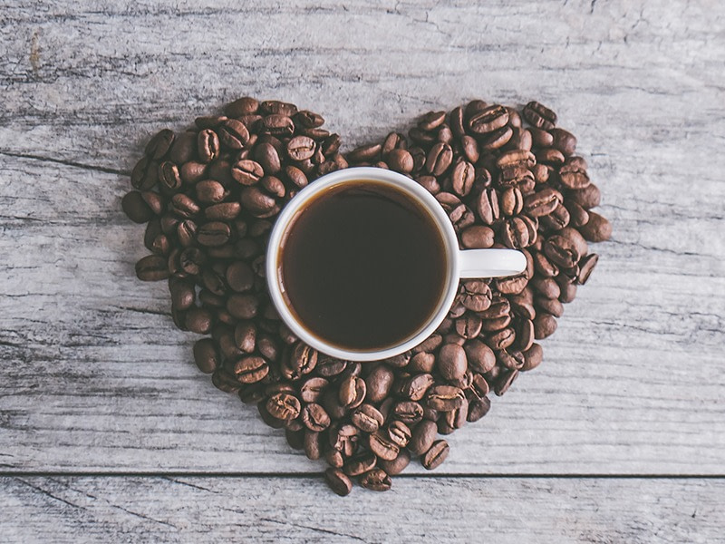 Bird's eye view of coffee beans arranged in the shape of a heart. In the centre of the heart is a mug filled with coffee