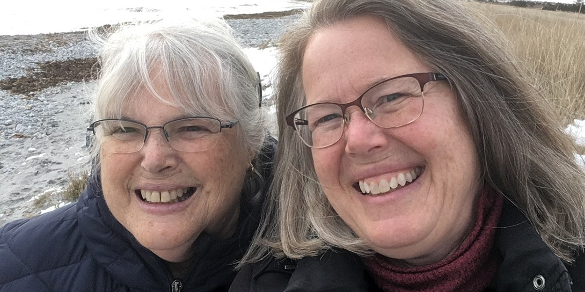 Two women, Aileen and Julie, smiling as they take a selfie on the beach